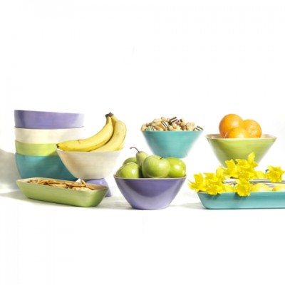 Set of coloured bamboo bowls filled with snacks and fruit.