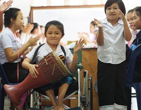 Girl in wheelchair playing drum.