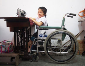 Girl in wheelchair sewing.